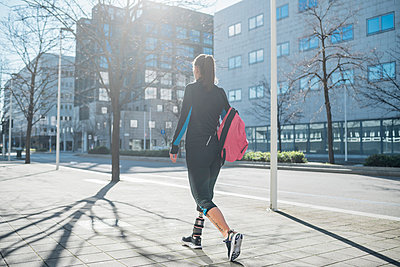 Sporty young woman with leg prosthesis walking in the city - p300m2170574 by Eugenio Marongiu