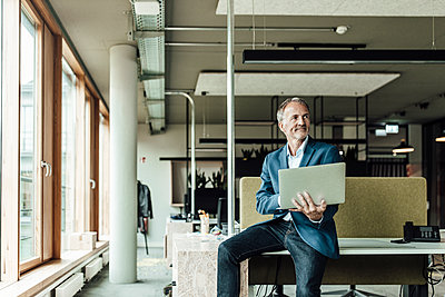 Businessman holding laptop while sitting on desk in office - p300m2265651 by Gustafsson