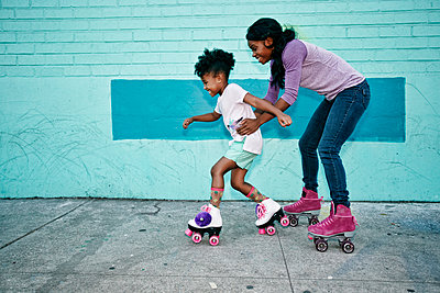 Black mother holding waist of daughter wearing roller skates - p555m1472949 by Peathegee Inc