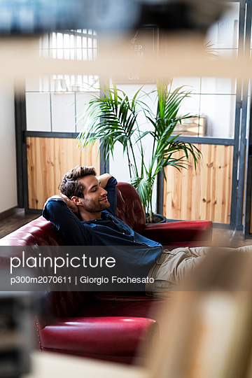 Young man sitting on couch with closed eyes - p300m2070611 by Giorgio Fochesato