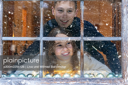 Smiling siblings looking at snowfall through window while sitting at home - p300m2256126 by Lisa und Wilfried Bahnmüller