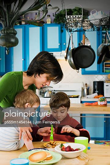 Hispanic mother and children having breakfast - p555m1454144 by Jon Feingersh