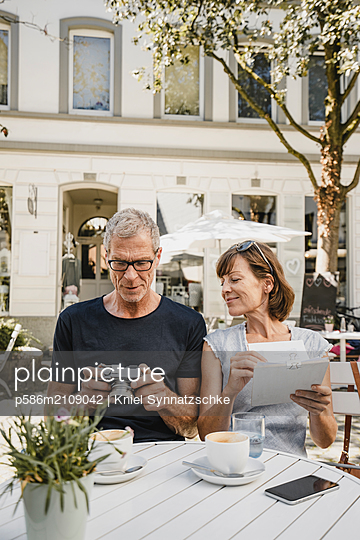 Mature couple in sidewalk cafe looking at photo camera - p586m2109042 by Kniel Synnatzschke