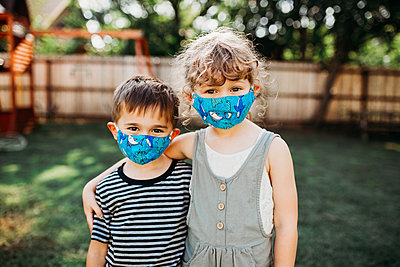 Two young kids standing outside together wearing homemade masks - p1166m2201685 by Cavan Images