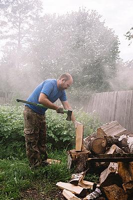 Man chopping wood,Tikhvin, SaintPetersburg, Russia - p1166m2202321 by Konstantin Trubavin