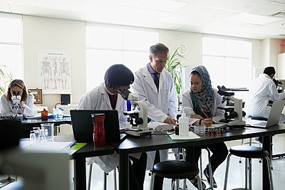 Professor helping students conducting scientific experiment in laboratory - p1192m1145700 by Hero Images