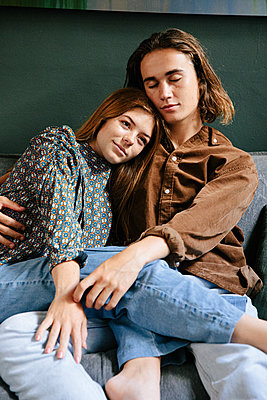 Teenage couple in love on a sofa - p1640m2242134 by Holly & John