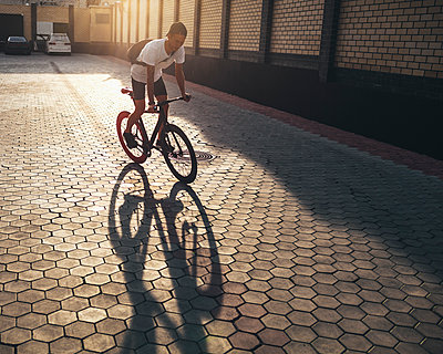 Young man riding fixie bike on backyard at sunset - p300m1505753 by Vasily Pindyurin