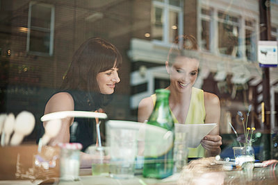 Smiling businesswomen discussing over document during meeting in coffee shop seen through window glass - p300m2220499 by LOUIS CHRISTIAN