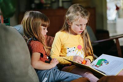 Sisters reading book on sofa - p312m2190427 by Matilda Holmqvist