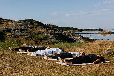 People practicing yoga at coast - p312m2208275 by Plattform