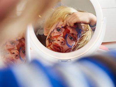 Junge schminkt sich im Spiegel - p358m1217514 von Frank Muckenheim
