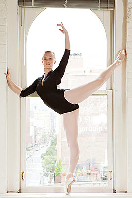 Ballerina poised in window - p9245522f by Image Source