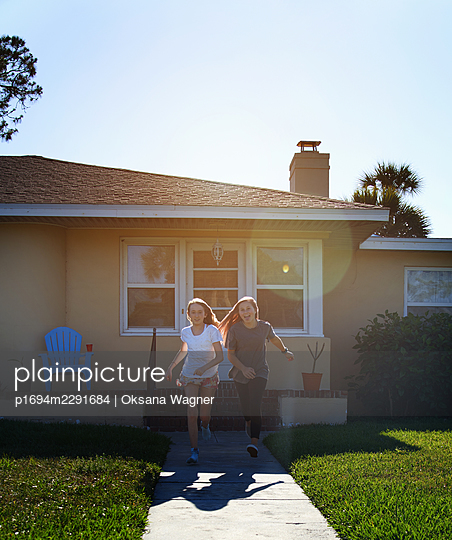 Two happy sisters enjoy running outside next to the house - p1694m2291684 by Oksana Wagner