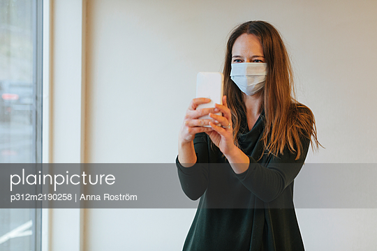 Woman wearing protective mask while taking selfie - p312m2190258 by Anna Roström