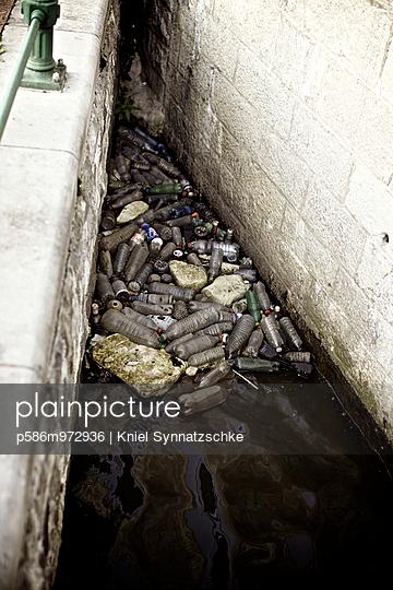 Weggeworfene Plastikflaschen in einem Kanal in der Stadt - p586m972936 von Kniel Synnatzschke