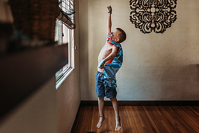 Young boy dressed as super hero with mask standing by window at home - p1166m2207778 by Cavan Images