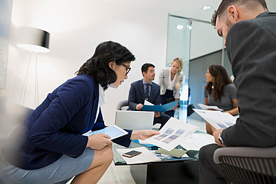 Business people reviewing paperwork in office lobby - p1192m1183762 by Hero Images