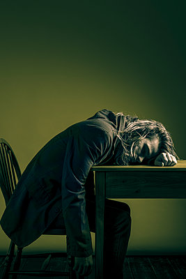 Young man with messy, long, blonde hair slumped onto a table. - p1433m1586832 by Wolf Kettler