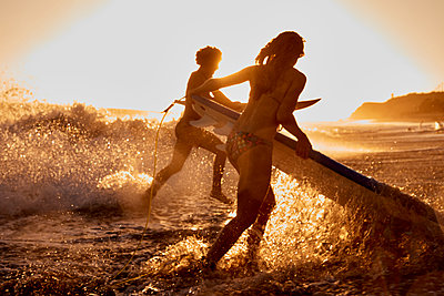 Surfers running into the sea at sunset - p300m1206161 by Fotoagentur