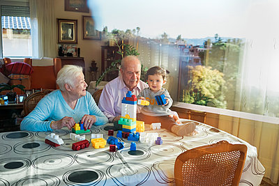 Great-grandparents and baby girl playing together with plastic building bricks at home - p300m1563064 by Gemma Ferrando