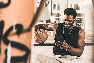 Smiling man with tattoos and basketball using smartphone and earphones - p300m1568465 by Uwe Umstätter