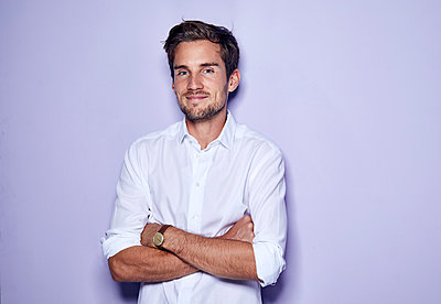 Portrait of content young businessman in front of purple background - p300m2059588 by Philipp Nemenz
