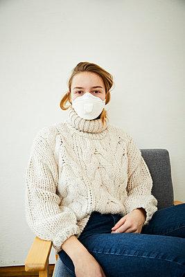 Portrait of blond woman wearing FFP2 mask at home - p300m2188586 by Sandra Bielmeier