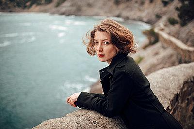 Caucasian woman standing on cliff over coastline - p555m1304707 by Marat Safin