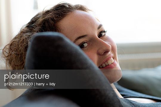 Junge Frau enstpannt sich auf dem Sofa - p1212m1217333 von harry + lidy