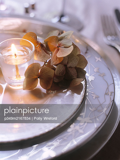 Lit candle with hydrangea on decorative plate - p349m2167834 by Polly Wreford
