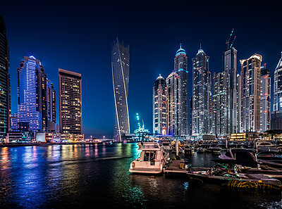 River and illuminated cityscape against blue sky at night - p1166m1142548 by Cavan Images