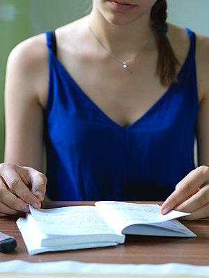Junge Frau blättert in einem Notizbuch - p1376m2101100 von Melanie Haberkorn