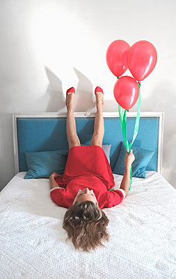 Woman in red dress lying on bed with balloons - p1521m2126544 by Charlotte Zobel