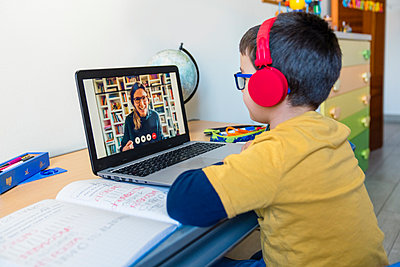 Boy listening to teacher through headphones during video call at home - p300m2198680 by Giorgio Magini