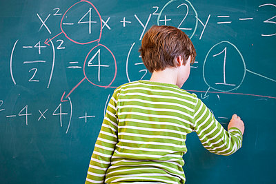 Rear view of primary schoolboy answering equation on classroom blackboard - p429m1226938 by RUSS ROHDE