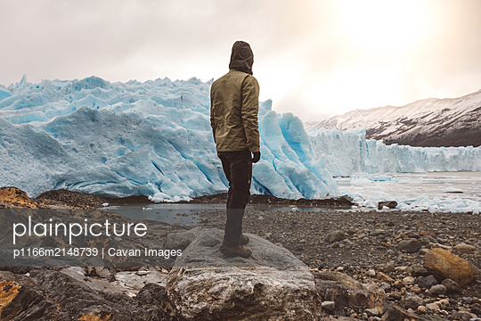 Unrecognizable man standing on boulder near glacier - p1166m2148739 by Cavan Images