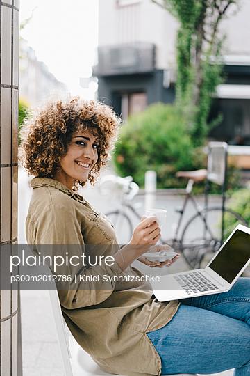 Woman working in a cafe, drinking coffee, using laptop - p300m2012786 von Kniel Synnatzschke
