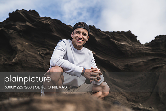 Smiling male tourist against on rock at El golfo, Lanzarote, Spain - p300m2257260 by SERGIO NIEVAS