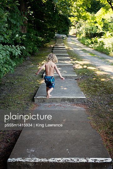 Caucasian boy climbing stairs near rural path - p555m1415934 by King Lawrence