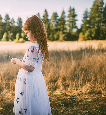 Side view of girl holding plant while standing on field at park - p1166m1530597 by Cavan Images