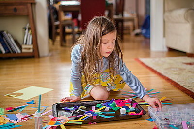 A little girl peacefully sits on living room floor with an art project - p1166m2096017 by Cavan Images