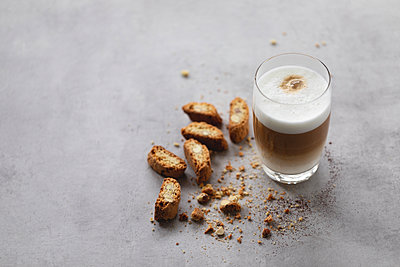 Latte macchiato in glass with cantuccini biscuits. - p1166m2162758 by Cavan Images