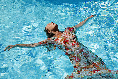 Blonde woman in sundress floating in pool - p1540m2122011 by Marie Tercafs