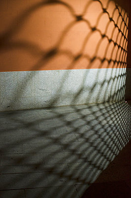 fence shadows are projected on a dark street corner - p1656m2238010 by Javier Martinez Bravo