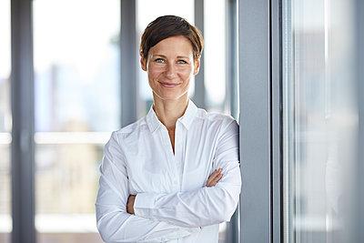 Portrait of smiling businesswoman in office - p300m2012961 von Rainer Berg