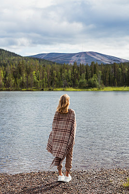 Finland, Lapland, woman wrapped in a blanket standing at the lakeside - p300m2060764 by Kike Arnaiz