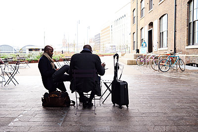 Two travelling businessmen sitting at pavement cafe working - p300m2083355 von Ivan Gener
