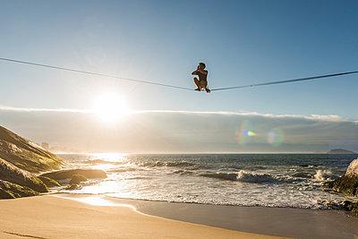 Man slacklining and waterlining during sunrise above Leblon Beach, Rio de Janeiro, Brazil - p343m1543667 by Vitor Marigo