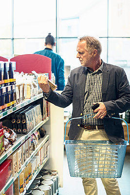 Mature man reading label on food package in supermarket - p426m1407398 by Kentaroo Tryman